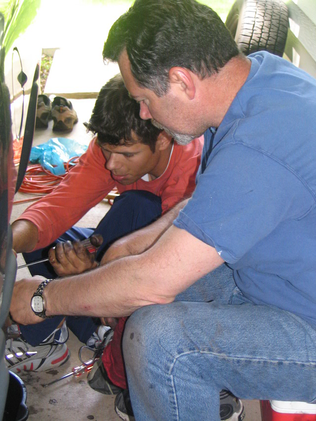 A father and son perform car repair.