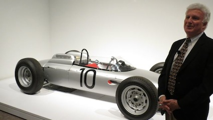 Curator Ken Gross stands next to a Porsche Type 804 Formula One race car.