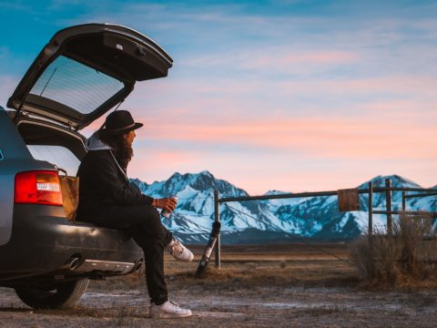 guy sitting on cars tail while looking at ranch